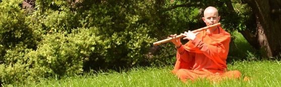 Swami playing flute in grass
